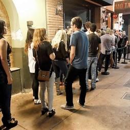Fiatalok a bár előtt. A beengedő ember a bejáratnál, mert lecsekkolják a látogatókat. Ennek oka az alkoholfogyasztás ellenőrzése.